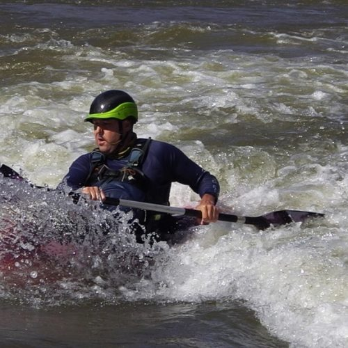 Kayaker surfing a wave